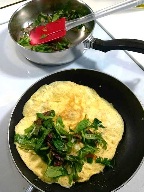 Power Greens Wilting in One Skillet While the Omelet Cooks